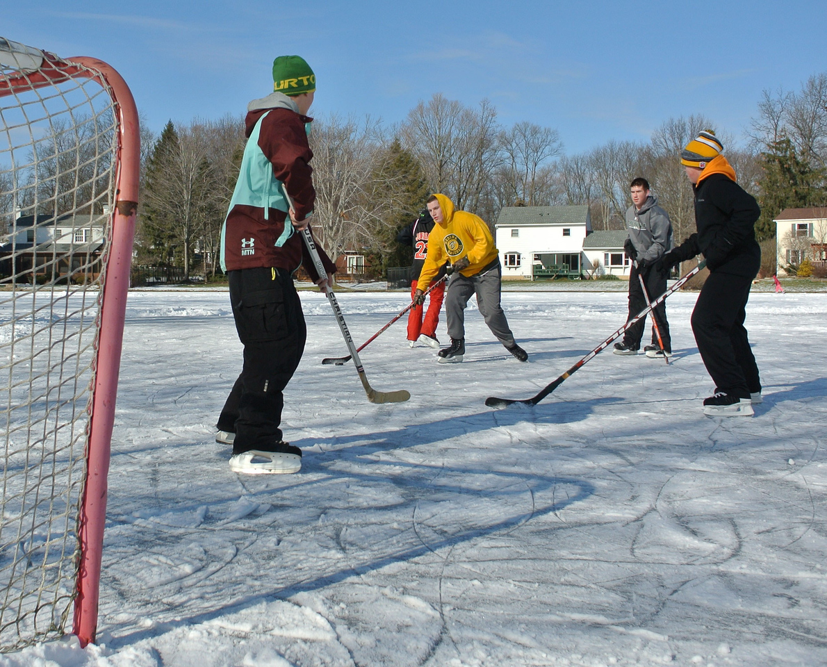 DAVID KNOX / GAZETTE Hunter Havekost (center, in gold sweatshirt) maneuvers with the puck during a friendly game of ice hockey on Sunday in Medina's Twin Oaks subdivision.