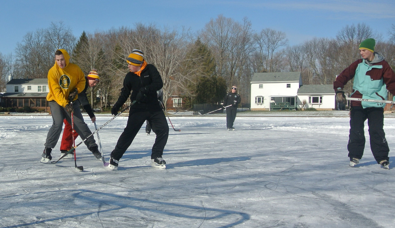 DAVID KNOX / GAZETTE Hunter Havekost (gold sweatshirt, left) duels with Brandon Leckie (Cleveland Cavaliers stocking hat, center) and Johnny Glad (next to Leckie) during a friendly ice hockey game in Medina's Twin Oaks subdivision on Sunday.