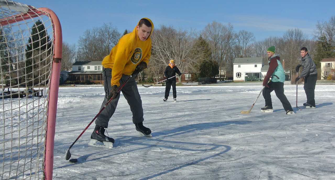 DAVID KNOX / GAZETTE Hunter Havekost scoops a hockey puck away from the net as Johnny Glad, Jack Lewarchick and Logan Kuczkowski await a pass on Sunday during a friendly game on ice in Medina's Twin Oaks subdivision.