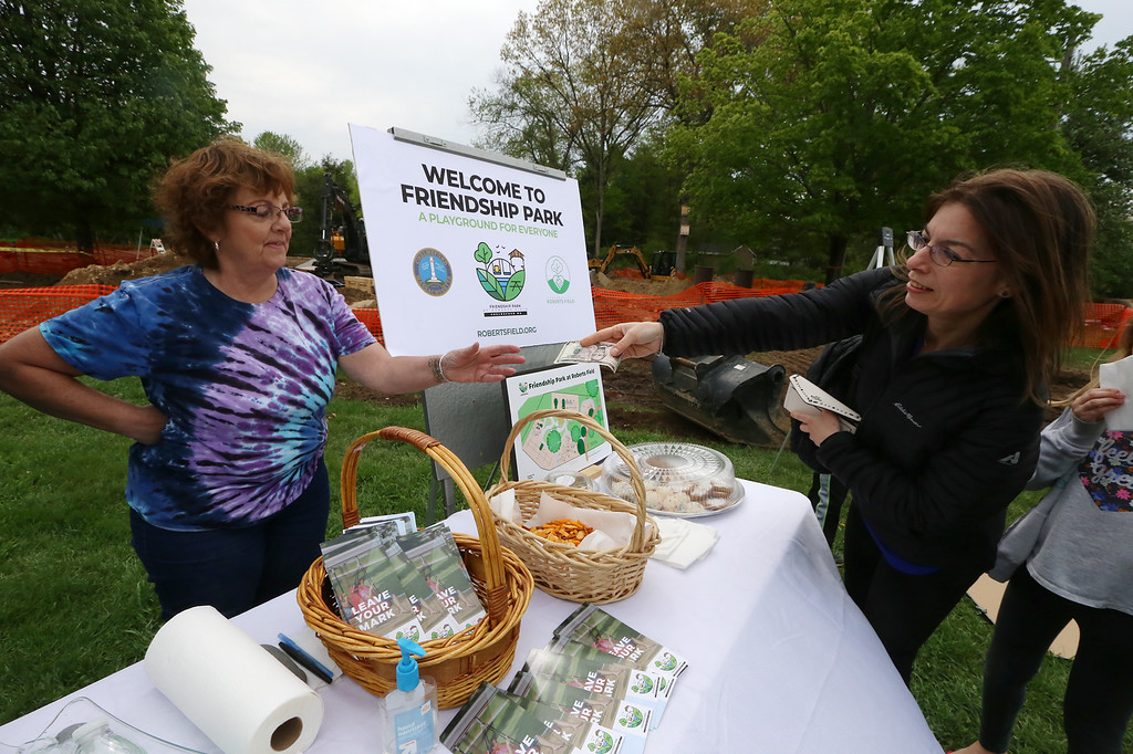 . Groundbreaking for Friendship Park, new playground at Roberts Field in Chelmsford. Volunteer Sandie Rainey, left, accepts a contribution for the project from Sandra Terranova. Both are from Chelmsford. (SUN/Julia Malakie)