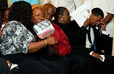 Ida Watkins-Sanders, second from left, releases her emotions as James Burroughs, far right, grieve for the loss of their son Joshua Caleb Cordero Burroughs during his funeral service Thursday afternoon at the Roy Davis Funeral Chapel.