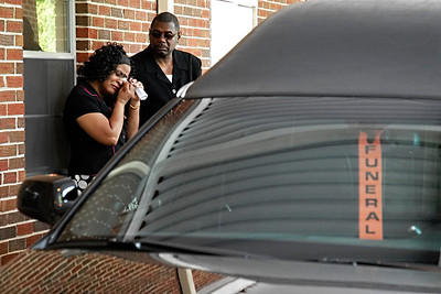 Chiquta Mitchell of Austell wipes away tears as she stands with her husband, Kirk, before the funeral of Joshua Caleb Burroughs began Thursday afternoon.  Their daughter, Cateria Hobbs, was the girlfriend of the late Mr. Burroughs.