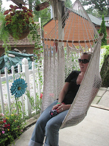 Morgan Rohrbaugh, of Medina, relaxes in a garden hammock on Sunday at a house in Chippewa Lake during the Medina County YWCA's annual Garden Tour. (Jennifer Pignolet/Gazette)