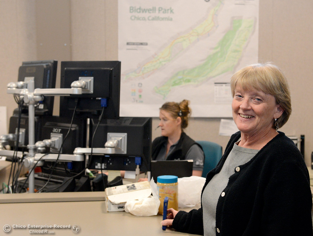 . Communications Manager Nancy Wilson smiles as she works in the Chico Police and Fire Dispatch Center located at the Chico Police Dept. in Chico, Calif. Wed. April 16, 2014. Dipatcher Tovi Brown is working in the backround. Being a dispatcher is a stressful job. They\'re the people who take all of the 911 calls, coordinate assistance to people who call, keep the officers safe and oversee how the Cico Police Department operates. (Bill Husa - Enterprise-Record)