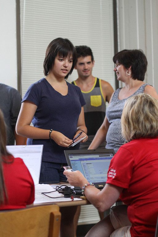 . Sara Uchimura, receives her new ID card from Nicole D\'Onofrio before moving her things into her new room in Whitney Hall at Chico State on Tuesday, August 20, 2013. (Frank Rebelo/Staff Photo)