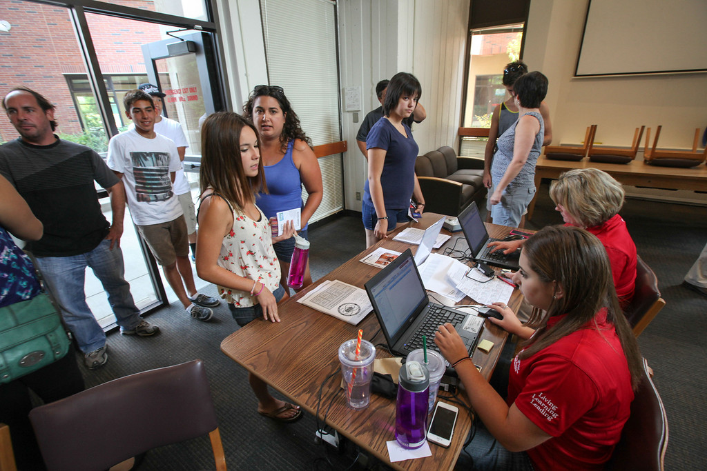 . Cassidy Pierce (left) and Sara Uchimura (right), receives their new ID card from Nicole D\'Onofrio (bottom left) and Jennifer Ross (Bottom Right) before moving their things into her new room in Whitney Hall at Chico State on Tuesday, August 20, 2013. (Frank Rebelo/Staff Photo)
