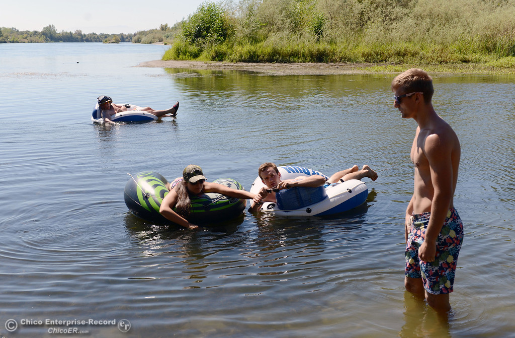 . Antonio Valoerga, 19, from Napa (back), Sacramento State student Mariah Braddock, 19, (left) and University of Oregon student Nathan Bergfelt, 19 (center) and Chico State student Dan Kelham, 20 (right) were four of the very few amount of people that came out to float on the Sacramento River, which authorities were enforcing an alcohol ban as part of Labor Day weekend Saturday, August 31, 2013 in Hamilton City, Calif.  (Jason Halley/Chico Enterprise-Record)