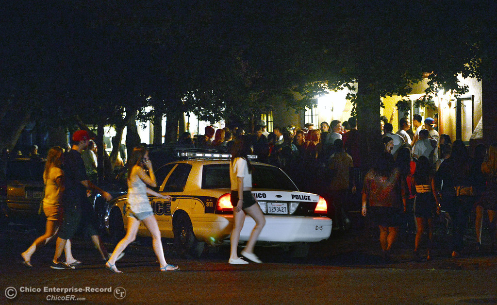 . People walk past a police car on 4th Street and Hazel Street near a party as the south campus area was fairly quiet before Labor Day weekend starting Friday, August 30, 2013 in Chico, Calif.  (Jason Halley/Chico Enterprise-Record)