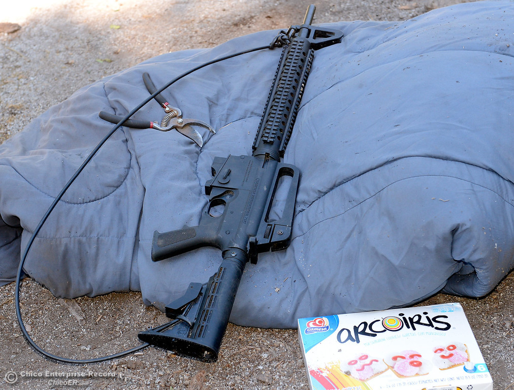 . This .22 caliber semi-automatic rifle and a box of cookies were found in an elevated and camoflaged platform near the grow area as several members of a multi agency Special Enforcement Unit eradicated nearly 7,300 marijuana plants from a remote area in Upper Concow Thursday, Aug. 15, 2013. A strap made of water line tubing is attached to the gun to help the user carry it. Two suspects were arrested in the marijuana garden. (Bill Husa/Staff Photo)