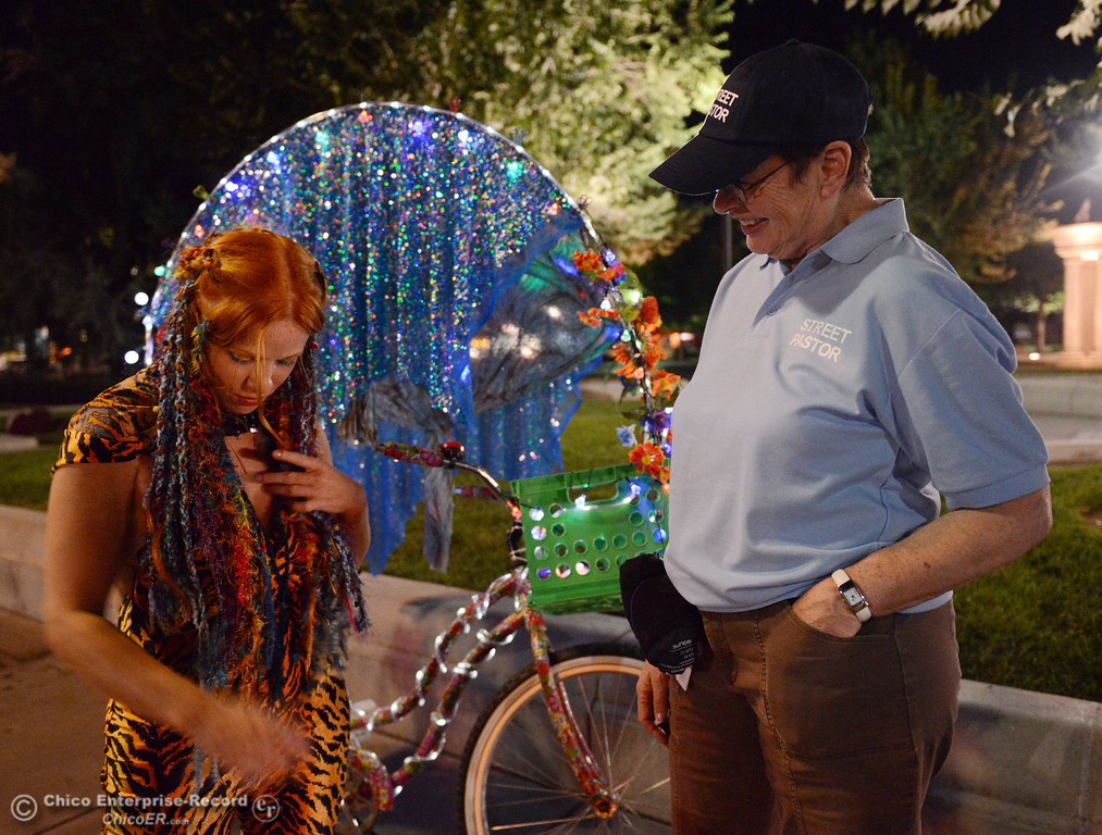 . Kelly Mosenfelder created a colorful light bike for burning man that she test rode around downtown as she talks with Nancy Calkins (right), that was part of the Street Pastors program Friday, August 23, 2013 in Chico, Calif.  (Jason Halley/Chico Enterprise-Record)
