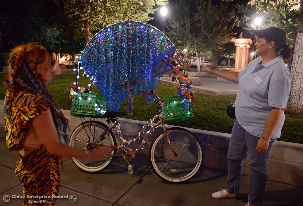 . Kelly Mosenfelder created a colorful light bike for burning man that she test rode around downtown as she talks with Judy Clark, that was part of the Street Pastors program Friday, August 23, 2013 in Chico, Calif.  (Jason Halley/Chico Enterprise-Record)