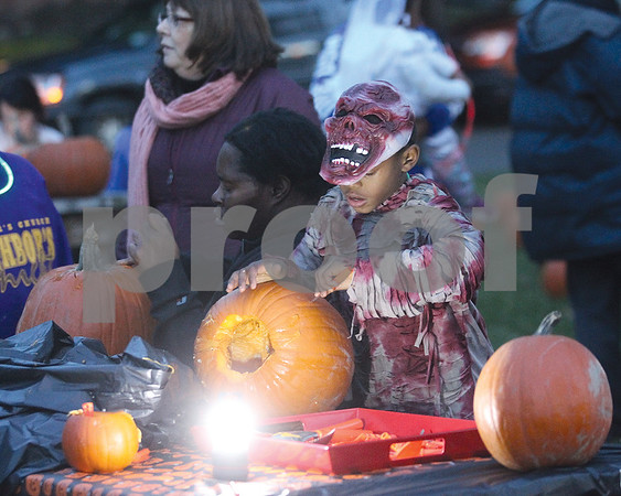 Spencer Tulis/Finger Lakes Times Key'son Johnson, 8, of Geneva carves a pumpkin at the recent Historic North neighborhood gathering held at the Genesee Street park.