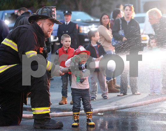 Spencer Tulis/Finger Lakes Times Emry McClusker, 2, of Geneva gets a hands-on experience with a firehose as part of the Geneva Fire Department's Demonstration and Open House Tuesday. Helping Emry out is Fireman Brian House. This week is Fire Prevention Week and included fire education with city schools.