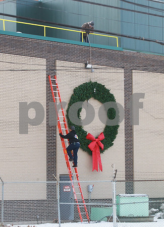 Spencer Tulis/Finger Lakes Times Workers from Evans Chemetics in Waterloo dismantle the large artificial Christmas wreath that has adorned the facility's exterior wall facing Routes 5 & 20 the past few months.