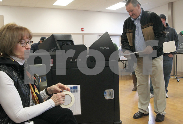 """Spencer Tulis/Finger Lakes Times Polling place worker Patti Bandy hands out """"I Voted"""" stickers at the town of Benton Town Hall Tuesday. Pictured casting his ballot is Jack Prendergast of Benton."""