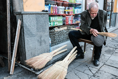 A one armed elderly man makes brooms at the Kutaisi Bazaar, Georgia.