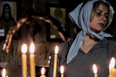 Faithfull Orthodox Christians worship in the Jvari Monastery Church of the Holy Cross, overlooking the town of Mtskheta.