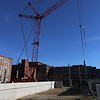 Work proceeds on Hamilton Canal District garage, with a giant luffing crane to lift precast columns and floors. The crane is holding a column in place while it's secured. (SUN/Julia Malakie)