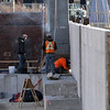 Work proceeds on Hamilton Canal District garage, with a giant luffing crane to lift precast columns and floors. The crane is holding this column in place while it's secured. (SUN/Julia Malakie)
