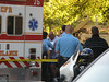 The father (civilian in blue-gray t-shirt and blue running shorts), who has just arrived, has a look of anguish as he approaches the ambulance to see his daughter. The area has been roped off with crime scene tape.