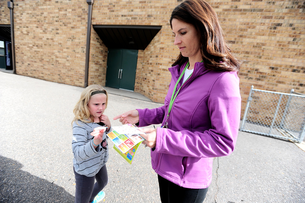. Sage Victory gets a sticker signifying one running lap from teach Mishel Reilly during a Girls on the Run of the Rockies meeting at Centennial Elementary School in Broomfield on Monday October 14, 2013. For more photos and a video from the group go to www.broomfieldenterprise.com Photo by Paul Aiken / The Broomfield Enterprise