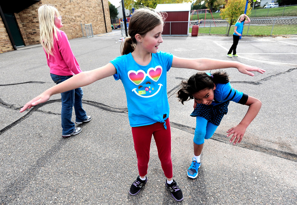 """. Kalani Gilman, center is rescued by Isabel Colombe during a Girls on the Run of the Rockies meeting at Centennial Elementary School in Broomfield on Monday October 14, 2013. The girls played a game of tag in which any tagged girl could be \""""unfrozen\"""" by another girl giving her a compliment in positive body images attributes and ducking under her arms. For more photos and a video from the group go to www.broomfieldenterprise.com Photo by Paul Aiken / The Broomfield Enterprise"""