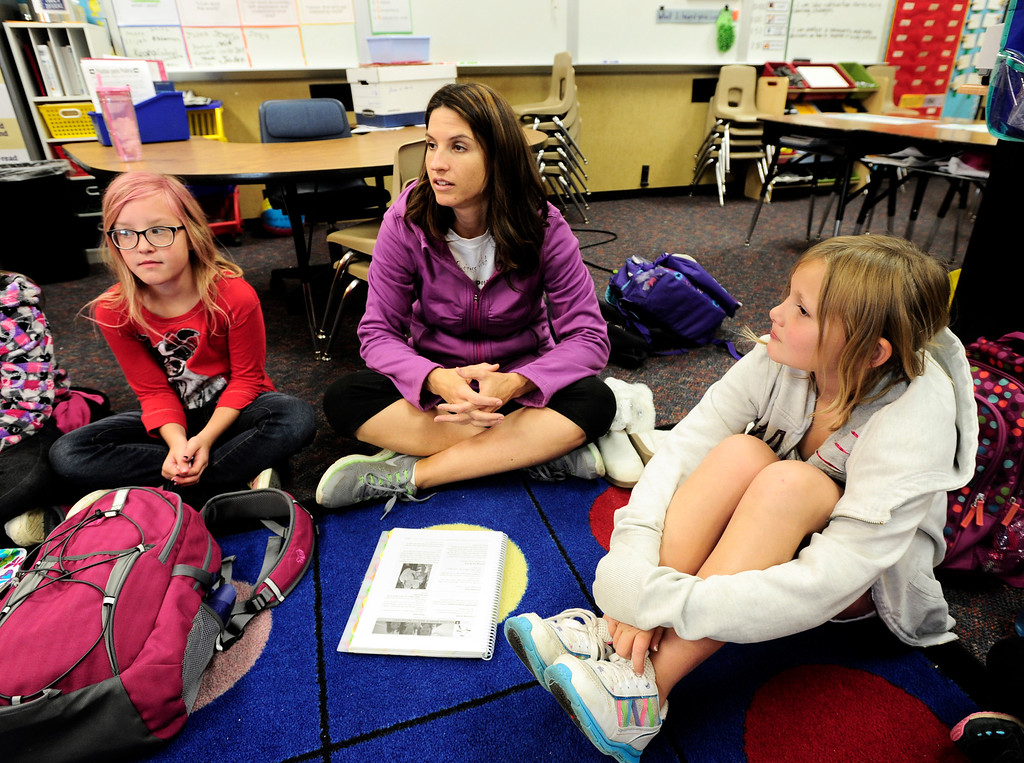 . Lily Pate, left and Madeline Smith listen to teacher Mishel Reilly, center,  talk about positive body image during a Girls on the Run of the Rockies meeting at Centennial Elementary School in Broomfield on Monday October 14, 2013. For more photos and a video from the group go to www.broomfieldenterprise.com Photo by Paul Aiken / The Broomfield Enterprise