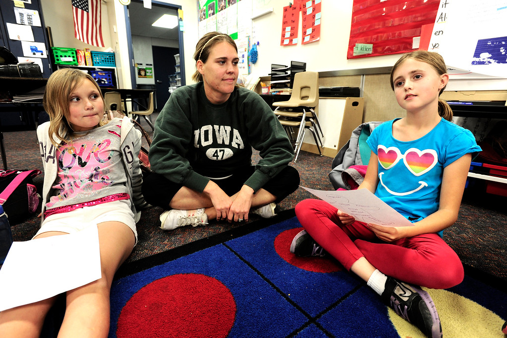 . Madeline Smith, left and teacher Jennifer Rosenfels, listen to Kalani Gilman read out her list of positive body image words during a Girls on the Run of the Rockies meeting at Centennial Elementary School in Broomfield on Monday October 14, 2013. For more photos and a video from the group go to www.broomfieldenterprise.com Photo by Paul Aiken / The Broomfield Enterprise