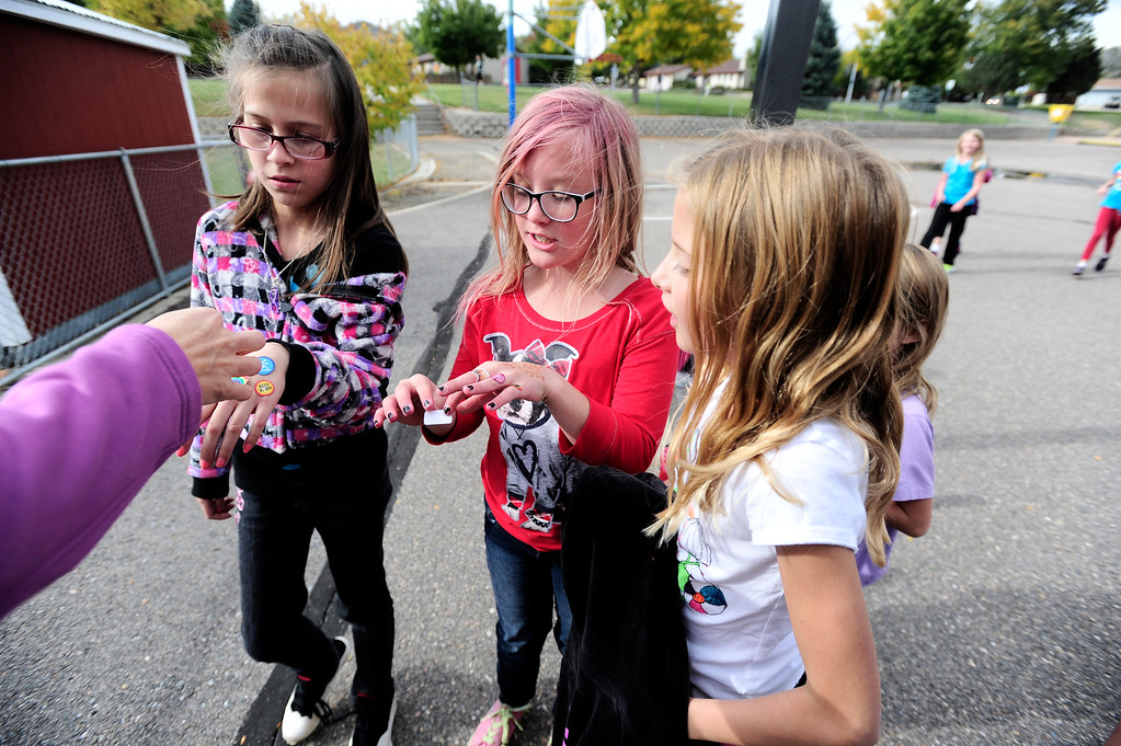 . From left to right Jasmine Bryant, Lilly Pate and Kassie Chapman each get stickers for running a lap around the playground during a Girls on the Run of the Rockies meeting at Centennial Elementary School in Broomfield on Monday October 14, 2013. For more photos and a video from the group go to www.broomfieldenterprise.com Photo by Paul Aiken / The Broomfield Enterprise