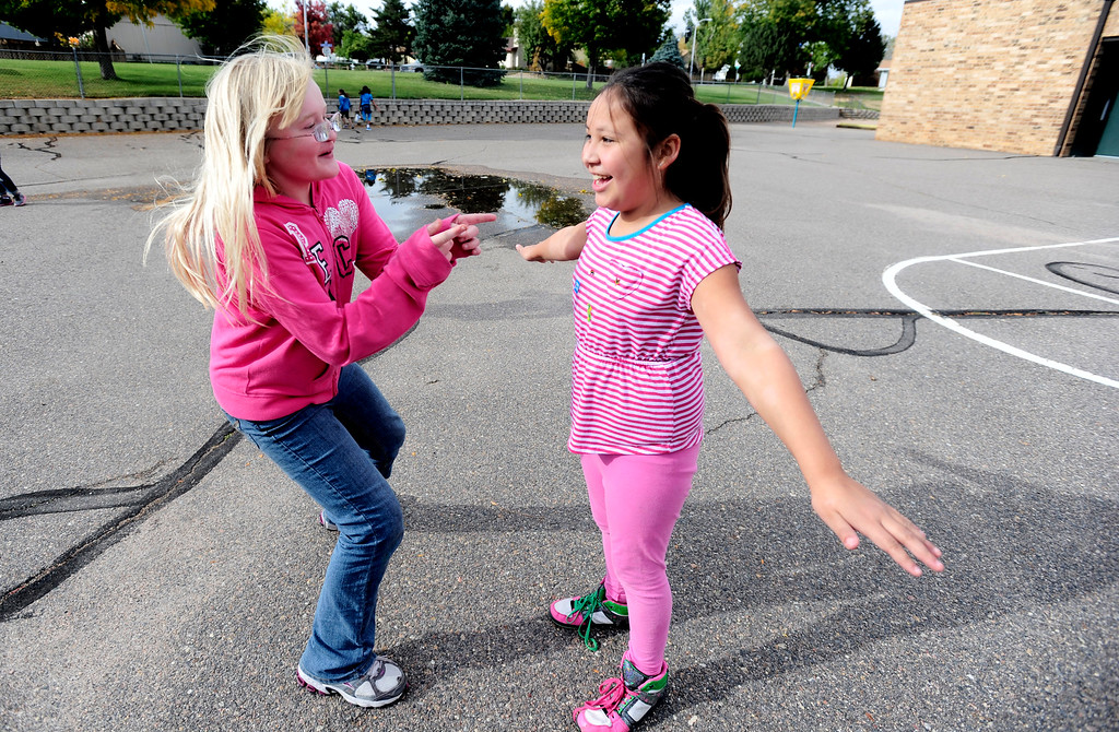 """. Rebekah Kleder gives a positive body image compliment to free a \""""frozen\"""" Jaymee Hawk in an tag game during a Girls on the Run of the Rockies meeting at Centennial Elementary School in Broomfield on Monday October 14, 2013. For more photos and a video from the group go to www.broomfieldenterprise.com Photo by Paul Aiken / The Broomfield Enterprise"""