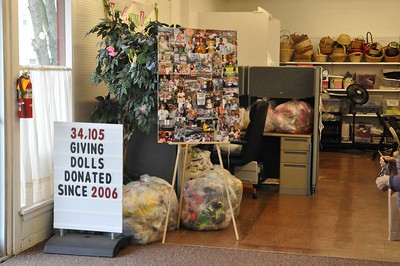 ASHLEY FOX / GAZETTE A collage of hundreds of children who have received dolls throughout the years, along with bagged dolls, waiting to be passed out to children.