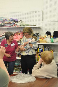 ASHLEY FOX / GAZETTE During the May 3 Open House, volunteers presented executive director Jan Householder with her own doll after the death of her father, who lost his battle with cancer a few weeks before. Householder has never had her own doll, even though she has been making them for a decade for children.