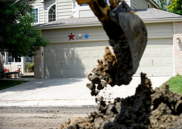 Construction workers pick work with the dirt in the road on Grayden Court in front of houses in Superior, Colorado July 10, 2012. Rachel Woolf/ For the Daily Camera