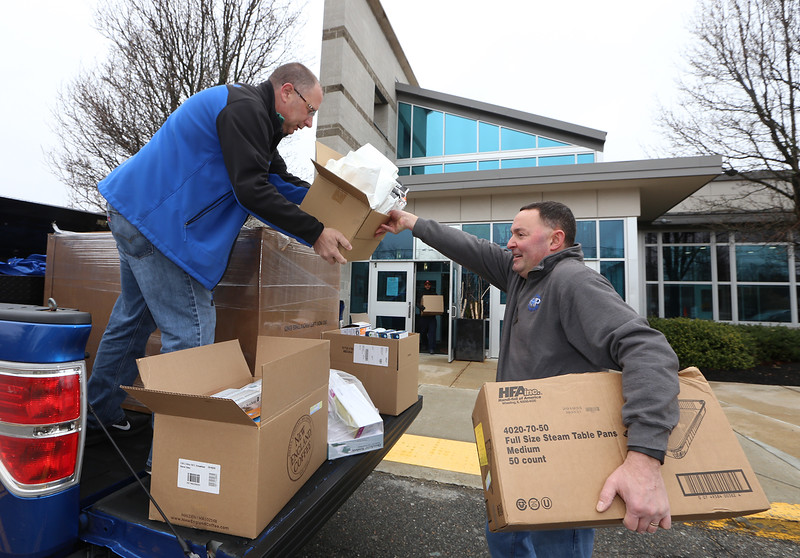 Staff from Greater Lawrence Technical High School help load gloves, masks and other items used in the school's vocational programs, being donated to the Greater Lawrence Family Health Center, to help them through the coronavirus-covid-19 shortage. Greater Lawrence Tech automotive technology instructor Michael Ouellette, right, hands cartons to Greater Lawrence Family Health Center facilities director Mike Kammer. (SUN/Julia Malakie)