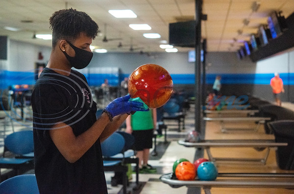 Green Acres Bowl employee Zane Williams sanitizes bowling balls left on the lanes during the business's first day back open after being closed due to the Covid-19 pandemic. The Tyler bowling alley has been a staple in the community for over five decades.