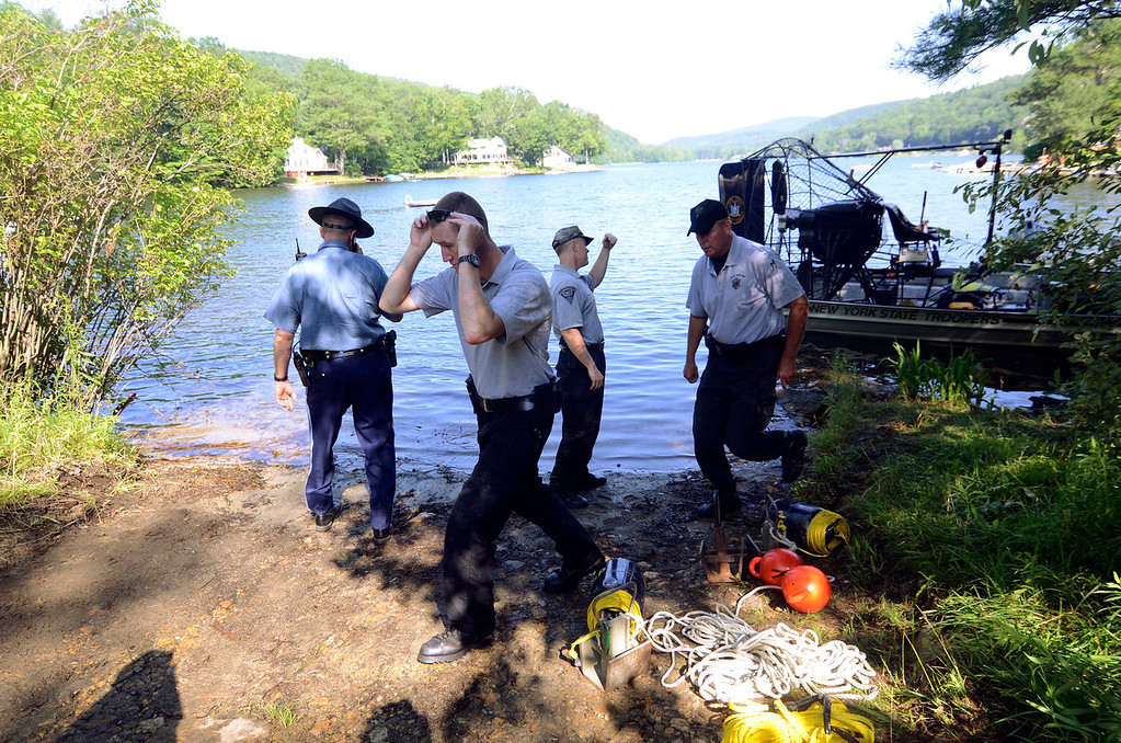 . Investigators for the Massachusetts State Police embark on a search for clues pertaining to the alleged abduction of James Lusher by Lewis Lent at Greenwater Pond in Becket, Tuesday July 16, 2013. Ben Garver / Berkshire Eagle Staff