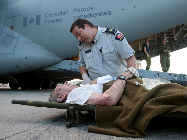 Surete du Quebec Sergeant Stephane Caputo speaks with an injured Canadian as he waits to be evacuated from Port-au-Prince, Haiti, Thursday, Jan. 14, 2010. Ninety-seven Canadians and five casualties were evacuated by the Canadian military Thursday.  (AP Photo/The Canadian Press, Adrian Wyld)