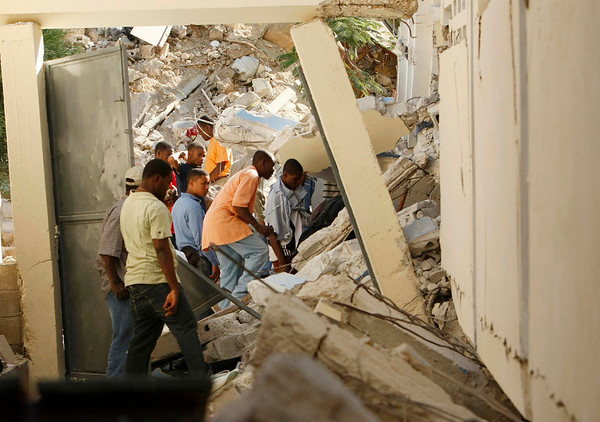 People look through the collapsed rubble of St. Gerard Church and School as they talk to a teacher trapped underneath in Port-au-Prince,  Thursday, Jan. 14, 2010. Several students and teachers died when the building collapsed after a 7.0-magnitude earthquake hit Haiti on Tuesday. (AP Photo/Gerald Herbert)
