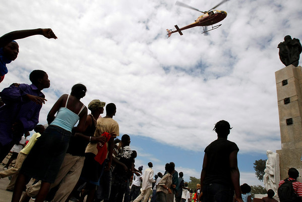 Earthquake survivors wave to a helicopter flying over Port-au-Prince, Haiti, Thursday, Jan. 14, 2010.  A 7.0-magnitude earthquake struck Haiti Tuesday. (AP Photo/Francois Mori)