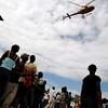 Earthquake survivors wave to a helicopter flying over Port-au-Prince, Haiti, Thursday, Jan. 14, 2010.  A 7.0-magnitude earthquake struck Haiti Tuesday. (AP Photo/Francois Mori)