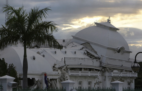 The sun sets behind the crumpled National Palace Port-au-Prince, Wednesday, Jan. 13, 2010. The  powerful earthquake that hit Haiti on Tuesday flattened the president's palace, the cathedral, hospitals, schools, the main prison and whole neighborhoods. (AP Photo/Lynne Sladky)