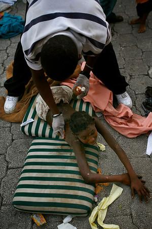 A volunteer gives first aid to an earthquake survivor in Port-au-Prince, Haiti, Thursday, Jan. 14, 2010.  A 7.0-magnitude earthquake struck Haiti Tuesday. (AP Photo/Ricardo Arduengo)