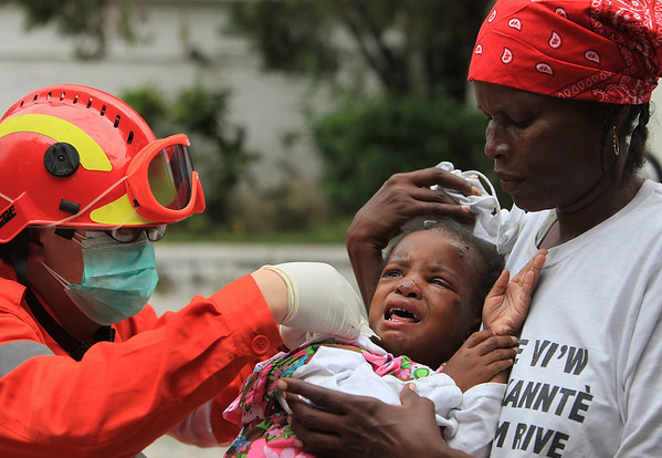 In this photo release by China's Xinhua News Agency, a doctor of the Chinese emergency rescue team, left, treats an injured child in Port-au-Prince, Haiti, Thursday, Jan. 14, 2010. Desperately needed aid from around the world slowly made its way Thursday into the capital after Tuesday's magnitude-7.0 earthquake. (AP Photo/Xinhua, Xing Guangli) ** NO SALES **