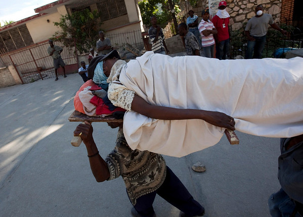 People carry an injured earthquake survivor in Port-au-Prince, Haiti, Thursday, Jan. 14, 2010.  A 7.0-magnitude earthquake struck Haiti Tuesday.  (AP Photo/Ramon Espinosa)