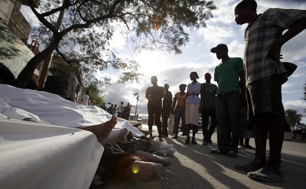 People look at earthquake victims lying on the street in the aftermath of a 7.0-magnitude earthquake in Port-au-Prince, Haiti, Wednesday, Jan. 13, 2010. (AP Photo/Lynne Sladky)