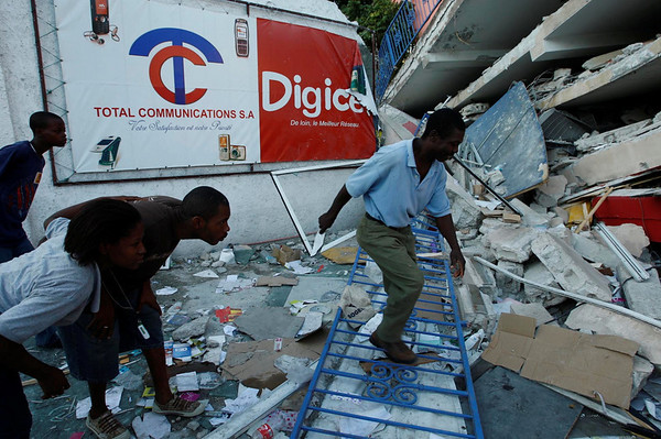 Men look for bodies buried under the rubble at the Digicel office that collapsed during the earthquake in Port-au-Prince, Haiti, Thursday, Jan. 14, 2010. (AP Photo/Carl Juste, The Miami Herald) MAGS OUT; NO SALES; TV OUT