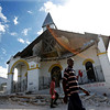 Survivors walk past a church destroyed in Tuesday's earthquake in Haiti's Capitol, Port-au-Prince Wednesday, Jan. 13, 2010. A falling down church in Port au Prince. (AP Photo/The Miami Herald, Patrick Farrell)       NO SALES, NO MAGAZINES, NO TV