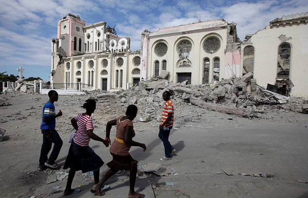 People walk by the Cathedral which collapsed during an earthquake in Port-au-Prince, Thursday, Jan. 14, 2010.  A 7.0-magnitude earthquake struck Haiti Tuesday. (AP Photo/Gregory Bull)