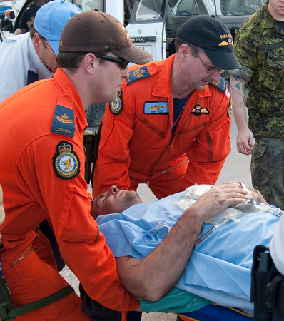 Paramedics transport an injured Canadian as they prepare him for transport to Canada at the airport in Port-au-Prince, Haiti, Thursday, Jan. 14, 2010. Ninety-seven Canadians and five casualties were evacuated by the Canadian military Thursday.  (AP Photo/The Canadian Press, Adrian Wyld)