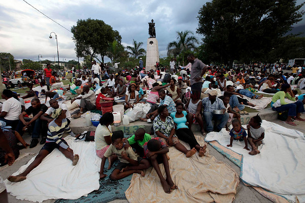 People sit at a park a day after the destructive earthquake in downtown Port-au-Prince, Wednesday, Jan. 13, 2010. The 7.0-magnitude earthquake that hit Haiti on Tuesday flattened the president's palace, the cathedral, hospitals, schools, the main prison and whole neighborhoods. (AP Photo/Gregory Bull)
